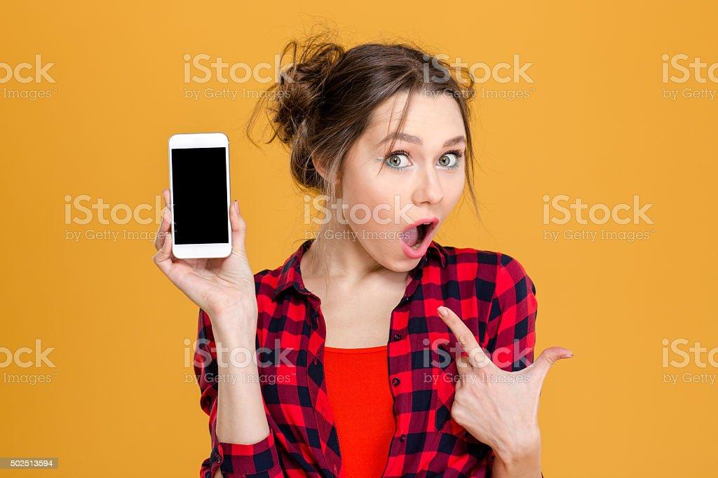 Amazed woman showing blank smartphone screen stock photo