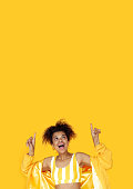 istock Amazed young african woman wear stylish yellow clothes point fingers look up at copy space, surprised excited black girl show upward advertise fashion sale on summer studio background vertical banner 1154833730