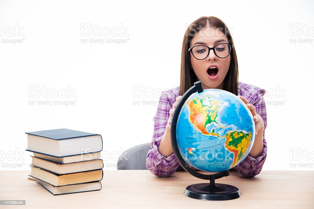 Amazed young female student looking at globe stock photo