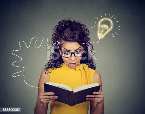istock Amazed young woman in glasses reading book comes up with an idea 668300082