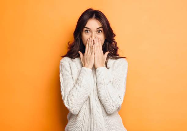 jonge vrouw verbaasd over oranje achtergrond - verrassing stockfoto's en -beelden