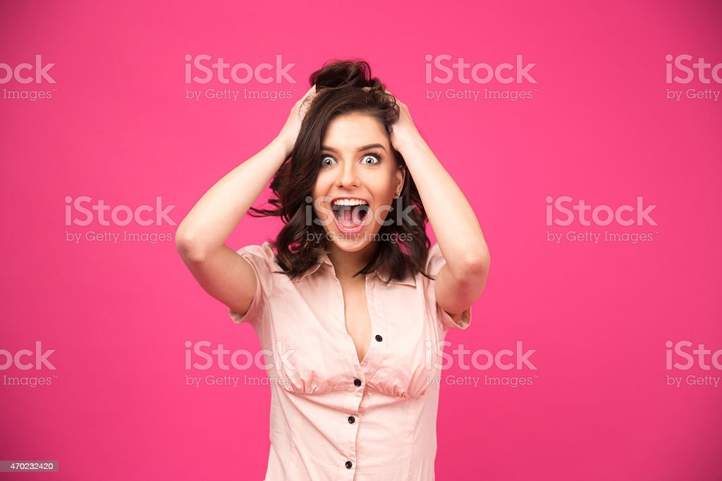 Amazed young woman shouting over pink background stock photo