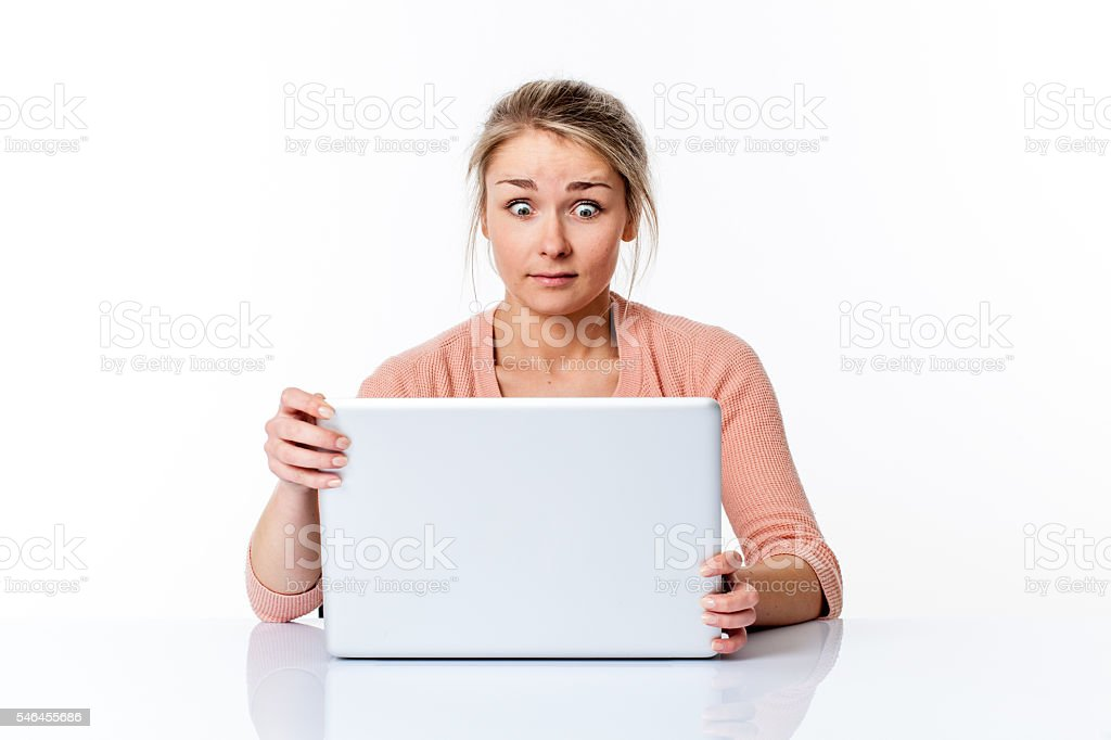 amazed young woman sitting at clean desk staring at computer stock photo