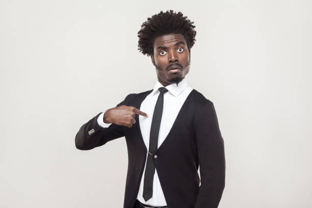 Amazement aloof afro man looking at camera. Studio shot, gray background Amazement aloof afro man looking at camera and pointing finger himself. Studio shot, gray background anchor athlete stock pictures, royalty-free photos & images