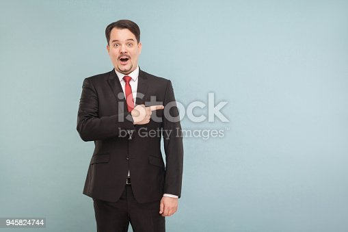istock Amazement businessman pointing finger to copy space 945824744