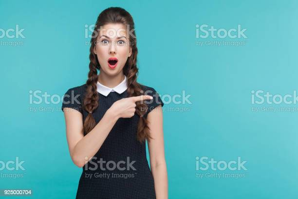 Amazement, wondered woman pointing finger right, at copy space. Studio shot, blue background