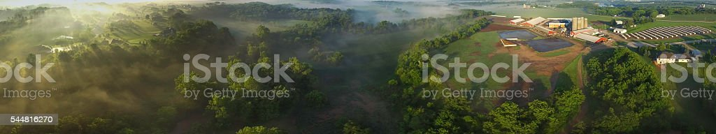 Amazing aerial panorama of foggy valley at sunrise stock photo