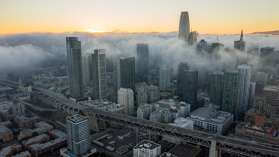 Aerial view of fog rolling over downtown at sunset.