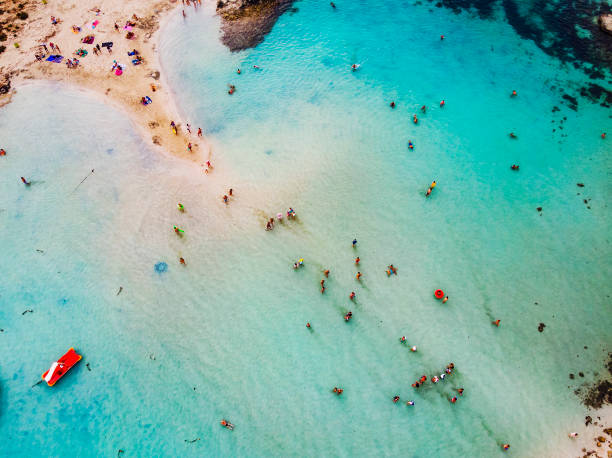 Amazing Aerial View from Above over Nissi Beach in Cyprus. Nissi Beach At high tide. Tourists relax on the beach. Crowded beach with lots of tourists. A popular place. stock photo