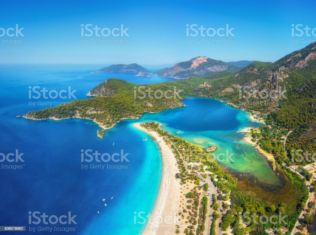 Amazing aerial view of Blue Lagoon in Oludeniz, Turkey. Summer landscape with mountains, green forest, azure water, sandy beach and blue sky in bright sunny day. Travel background. Top view. Nature stock photo