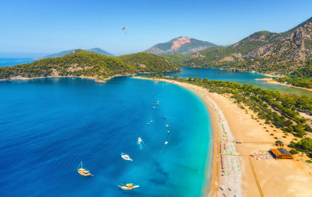 Amazing aerial view of Blue Lagoon in Oludeniz, Turkey. Summer landscape with sea spit, boats and yachts, green trees, azure water, sandy beach in sunny day. Travel. Top view of national park. Nature Amazing aerial view of Blue Lagoon in Oludeniz, Turkey. Summer landscape with sea spit, boats and yachts, green trees, azure water, sandy beach in sunny day. Travel. Top view of national park. Nature turkish stock pictures, royalty-free photos & images
