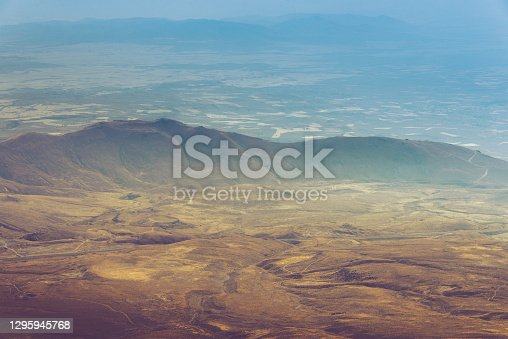 istock Amazing aerial view of desert, stone hills, and distant mountains layers range. Wilderness background. Vintage toning effect. Near Mount Erciyes. Kayseri, Turkey. 1295945768