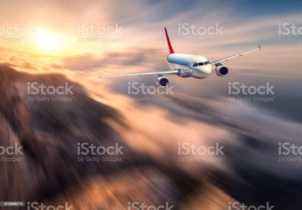 Amazing airplane mith motion blur effect is flying over low clouds at sunset. Landscape with passenger airplane, blurred clouds, mountains, sun. Passenger aircraft. Business travel. Commercial plane stock photo