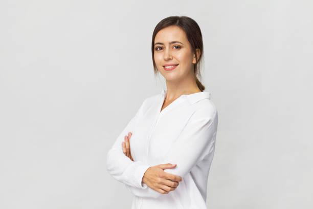 Erstaunlich und fröhlich lächelnde Brünette mit verschränkten Armen im weißen Hemd Studioaufnahme, isoliert auf weiss – Foto