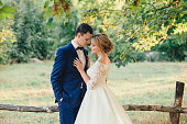 Amazing attractive young couple with closed eyes in wedding day. bride in elegant white long dress and blue bouquet in hand, the groom in a blue fashionable business suit, standing near the lawn.