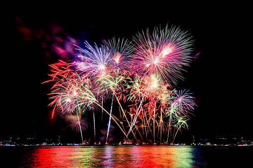 istock Amazing beautiful colorful fireworks display on celebration night, showing on the sea beach with multi color of reflection on water 1188842672