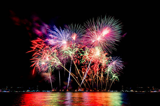 Amazing beautiful colorful fireworks display on celebration night, showing on the sea beach with multi color of reflection on water Amazing beautiful colorful fireworks display on celebration night, showing on the sea beach with multi color of reflection on water modern period stock pictures, royalty-free photos & images