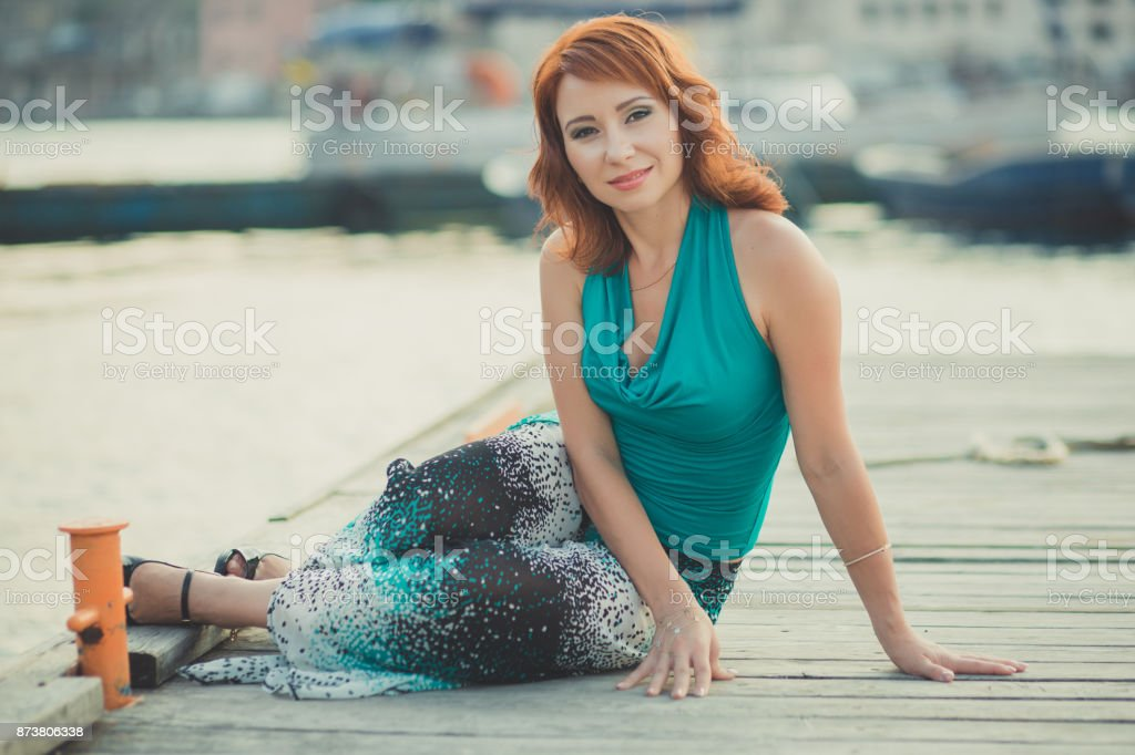 Amazing beautifull lady girl woman with red flame hair wearing fancy fashion green clothes posing sitting on wooden pier jetty wth port boats on background Adoring scene of sea mermaid stock photo
