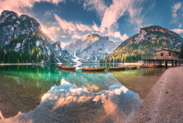 Amazing Braies lake at sunrise in autumn in Dolomites, Italy. Landscape with mountains, sky with clouds, boats, water with reflection, trees with colorful leaves. Lake in fall. Italian alps. Panorama stock photo