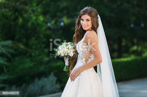 istock Amazing bride in beautiful white wedding dress hold bouquet of flowers in her hands. Concept of clothes and floristics 935445070