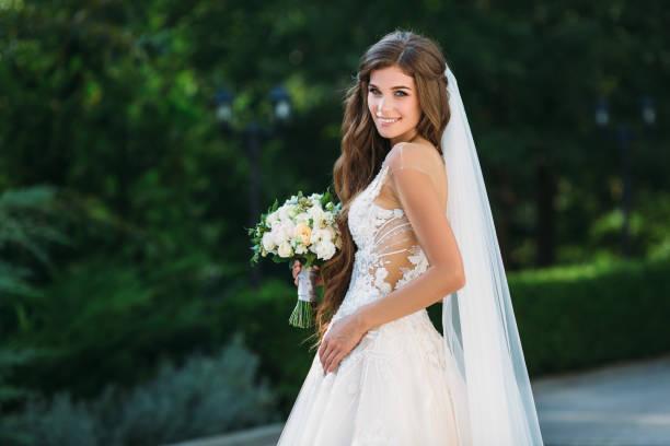 niesamowita panna młoda w pięknej białej sukni ślubnej trzymać bukiet kwiatów w rękach. koncepcja ubrań i florystyki - panna młoda zdjęcia i obrazy z banku zdjęć