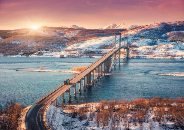 Erstaunliche Brücke während des Sonnenuntergangs in Lofoten Inseln, Norwegen. Aerial Winterlandschaft mit Autos auf der Straße, blaues Meer, Bäume, schneebedeckte Berge, bunte orangefarbenen Himmel mit Wolken und Sonne. Nordische Landschaft – Foto