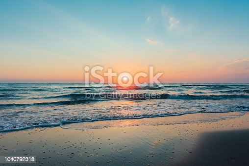 Amazing colorful sunrise at sea, early morning on the beach