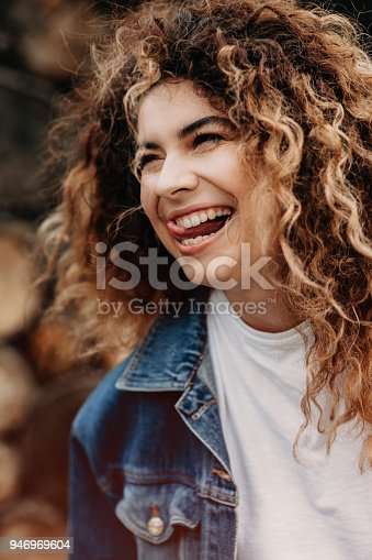 istock Amazing curly woman dressed in denim jacket is laughing and looking away. 946969604