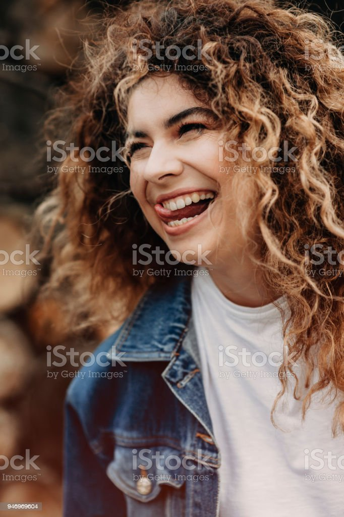 Amazing curly woman dressed in denim jacket is laughing and looking away. stock photo