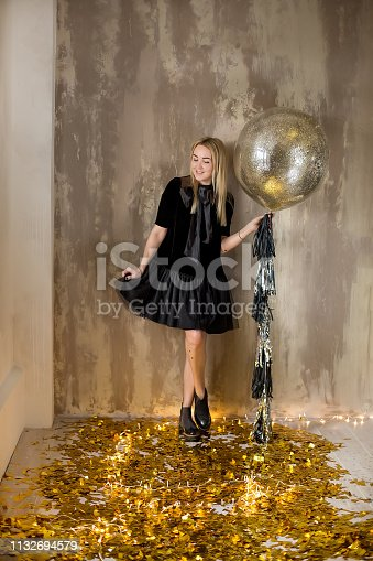 istock Amazing cute lady celebrating new year birthday party, posing in gold shine background and throwing colorful confetti with silver baloons. 1132694579