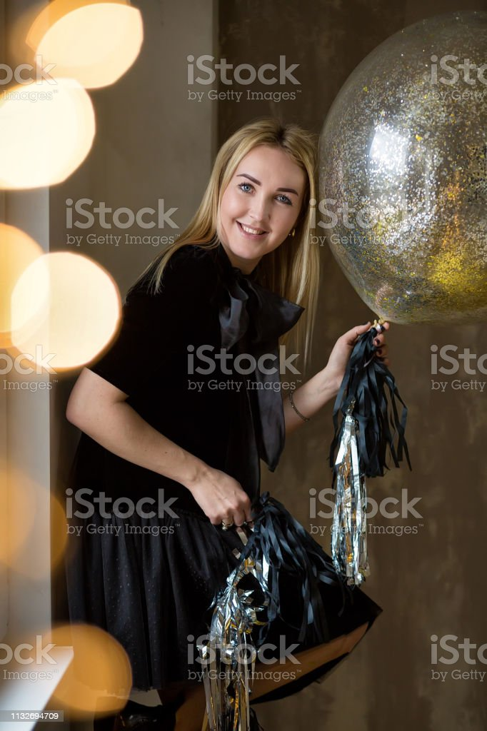 Amazing cute lady celebrating new year birthday party, posing in gold...