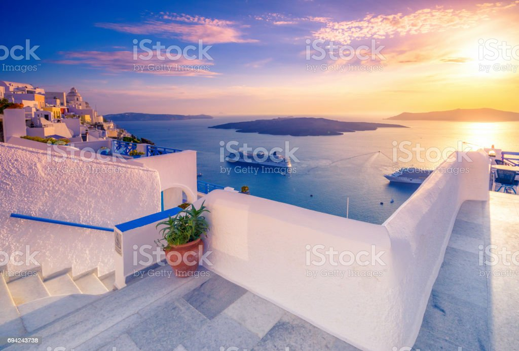 Amazing evening view of Fira, caldera, volcano of Santorini, Greece with cruise ships at sunset. Cloudy dramatic sky. stock photo