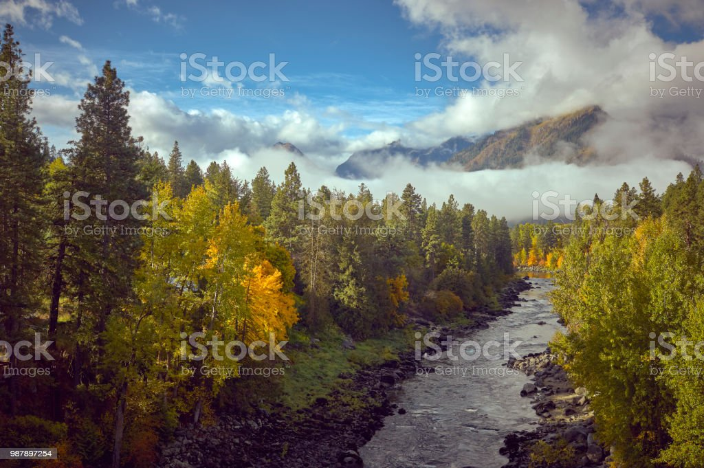 Amazing fall colors, blue sky and giant white clouds overlooking the Wenatchee River outside of Leavenworth Washington stock photo