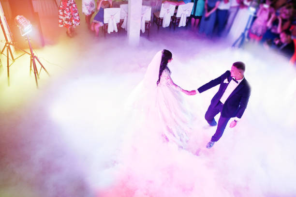 amazing first wedding dance of newlywed with different colourful light and heavy smoke on restaurant. - dance floor stock photos and pictures