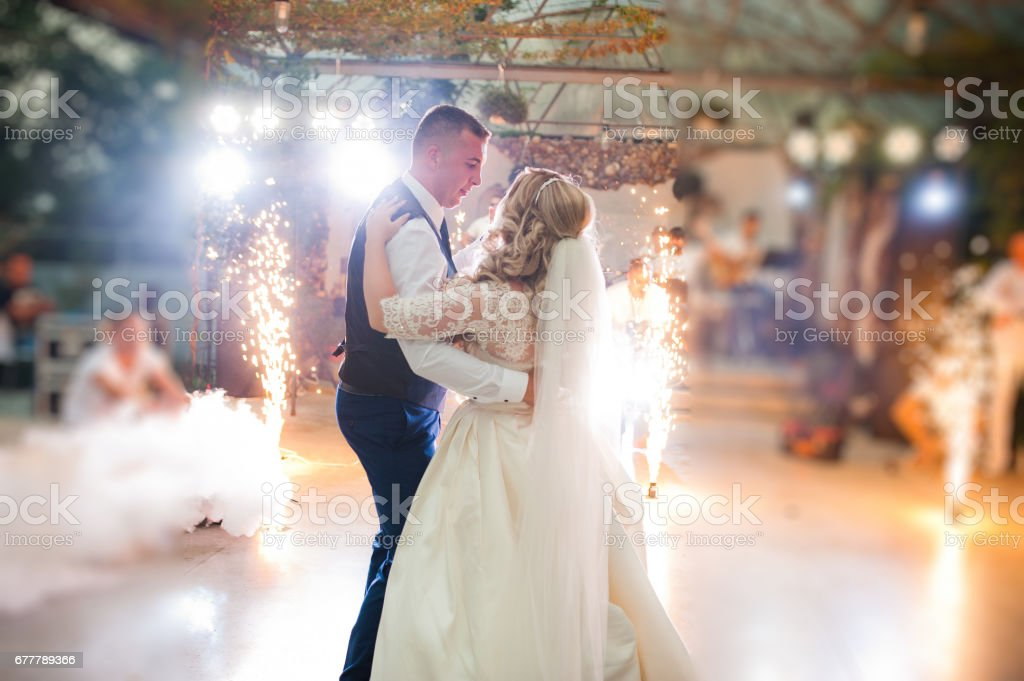 Amazing first wedding dance of newlyweds at heavy smoke and fireworks. royalty-free stock photo
