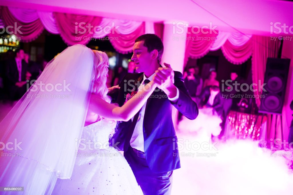 Amazing first wedding dance of newlyweds on low pink light and heavy smoke stock photo