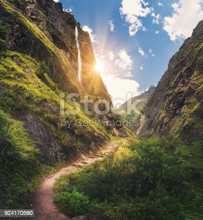 Amazing Himalayan mountains covered green grass, high waterfall, beautiful path, green trees, blue sky with yellow sun and clouds in Nepal at sunset. Mountain canyon. Travel in Himalayas.Landscape