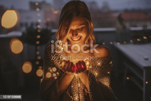 Young, smiling woman standing outdoors on the decorated terrace of her apartment and holding string lights