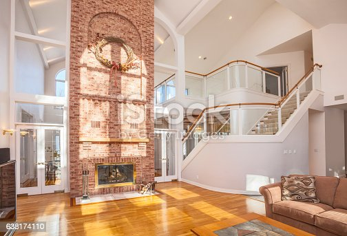 istock Amazing home interior with brick fireplace and spectacular glass staircase. 638174110