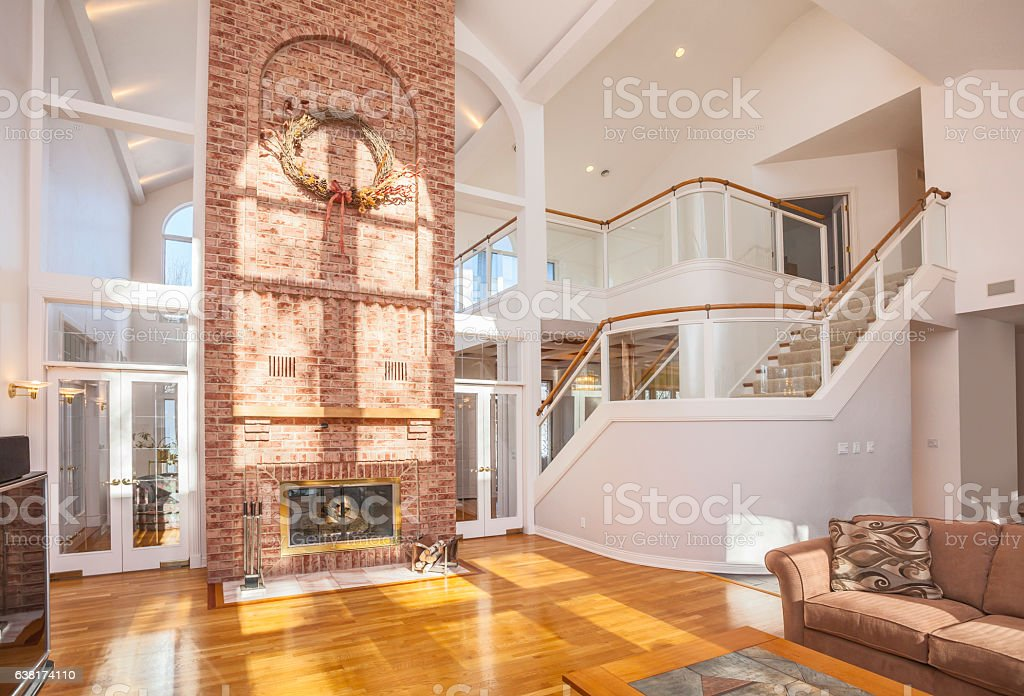 Amazing home interior with brick fireplace and spectacular glass staircase. stock photo
