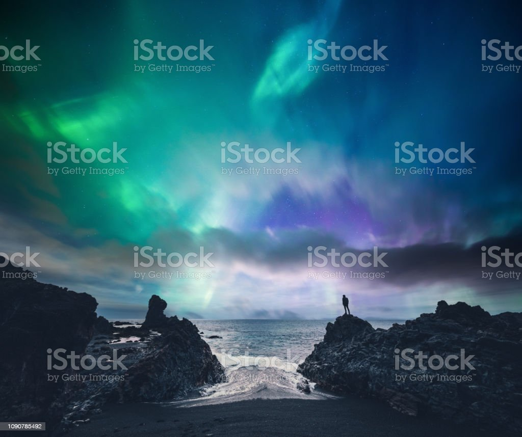 Amazing Iceland Man standing on the rock at the beach watching northern lights (Iceland). Adult Stock Photo