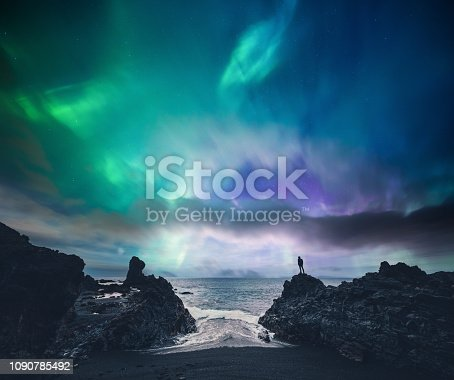 Man standing on the rock at the beach watching northern lights (Iceland).