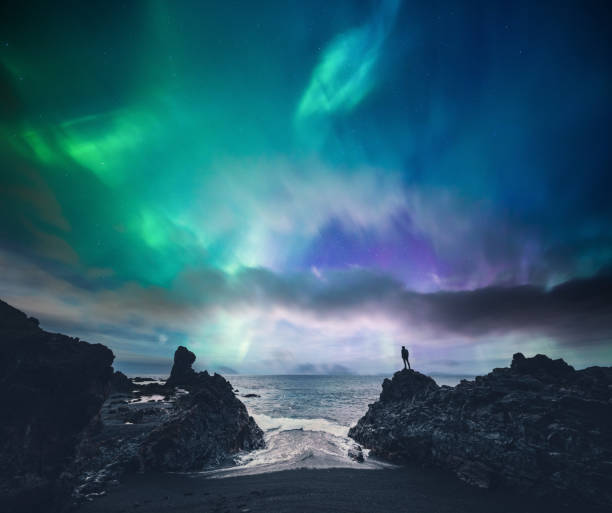 Amazing Iceland Man standing on the rock at the beach watching northern lights (Iceland). awe stock pictures, royalty-free photos & images