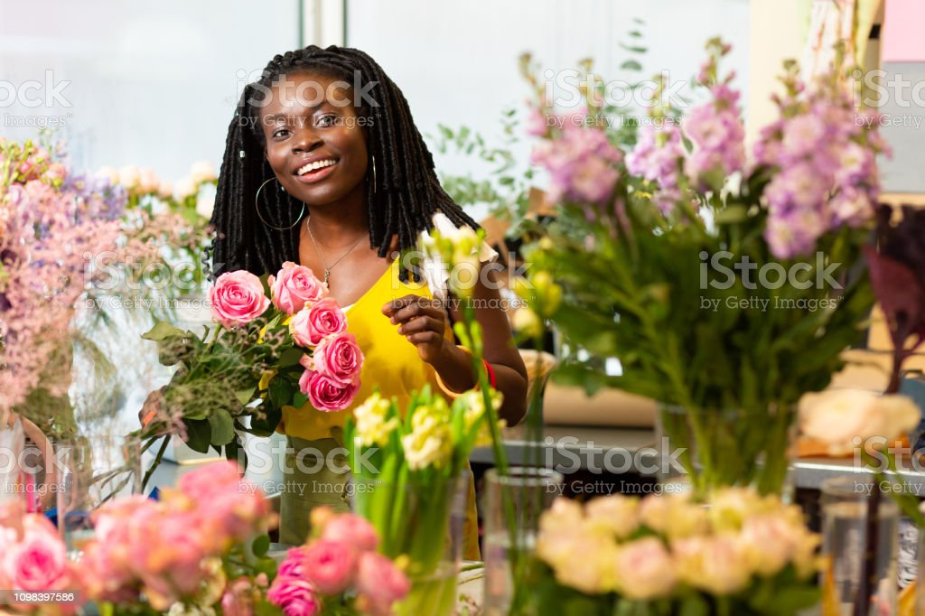 Friendly smile. Kind florist expressing positivity while holding...
