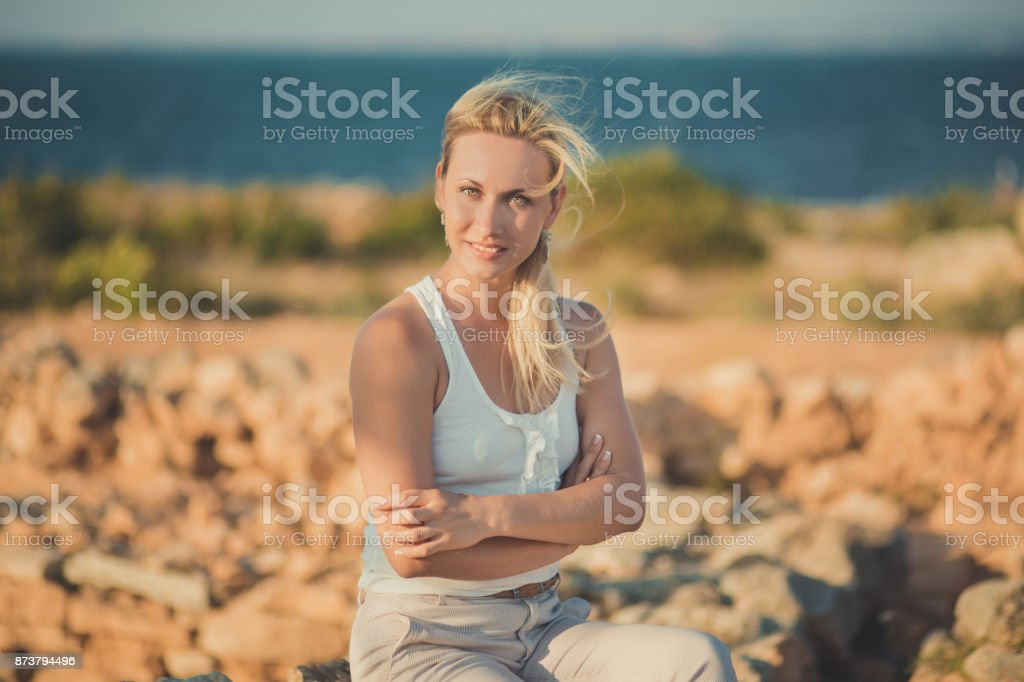 Amazing lady blond woman in light white stylish clothes sexy posing on sea side beach air.Sparkler girl looking to camera on ancient city stones blue ocean on background. stock photo
