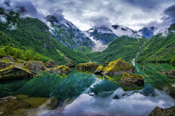 Amazing lake on a background of mountains and glacier. Norway. Beautiful landscape. Artistic picture. Beauty world. Amazing lake on a background of mountains and glacier. Norway. Beautiful landscape. Artistic picture. Beauty world. norwegian culture stock pictures, royalty-free photos & images
