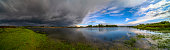Amazing landscape of nature before thunder storm. Dark clouds cover blue sky at wild river. Incredible weather panorama