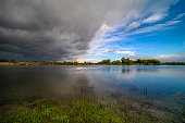 Amazing landscape of nature before thunder storm. Dark clouds cover blue sky at wild river. Incredible weather