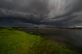 Amazing landscape of nature before thunderstorm. Dark clouds above wild river. Dramatic weather