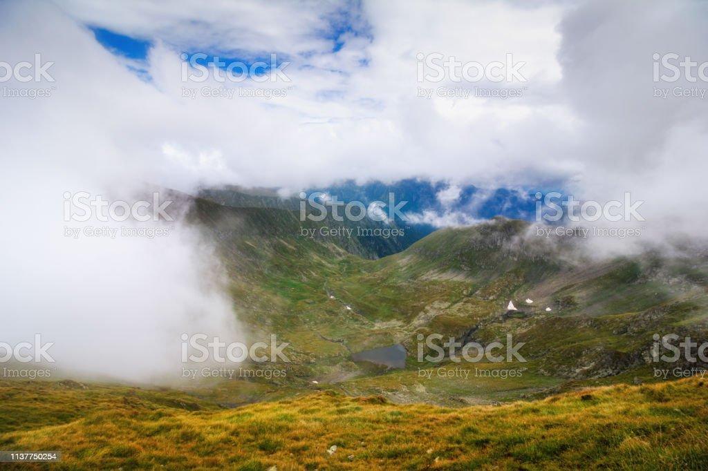 Erstaunliche Landschaft der Sommerberge. Blick auf Nebel und niedrige Wolken über den Fagaras-Bergen sind die höchsten Berge der Südkarpaten. Rumänien. Reisehintergrund. – Foto